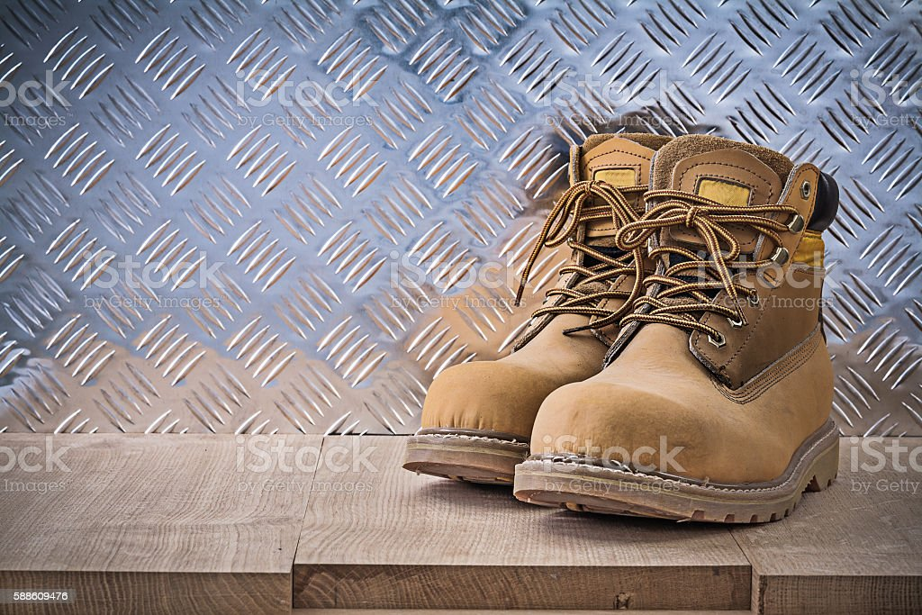 Pair of safety lace boots wooden board fluted metal sheet stock photo