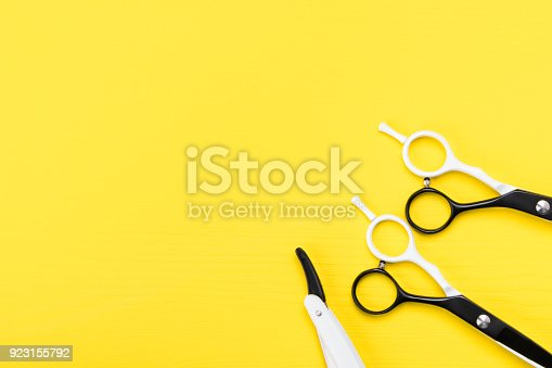 istock pair of scissors for a hairstyle lay in a corner on a yellow background 923155792