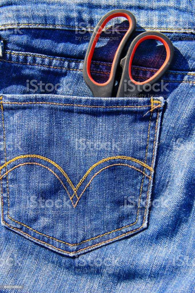 Pair of scissors in pocket of blue jeans stock photo