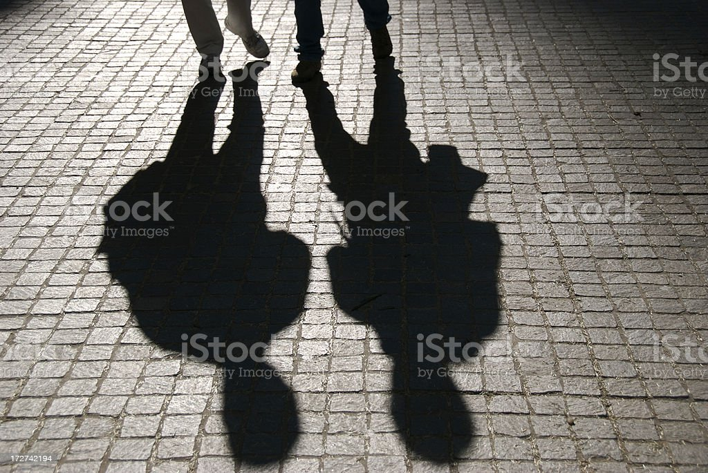 Pair of Shadows Walk on Dark Cobblestone Street royalty-free stock photo
