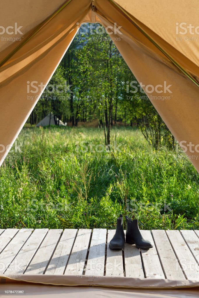 Pair of shoes near canvas tent at forest stock photo