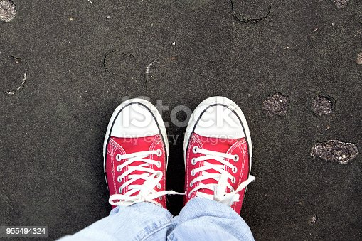 Pair of red shoes standing on a road