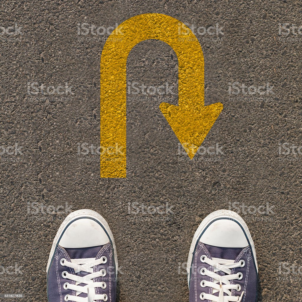 Pair of shoes standing on a road with traffic sign stock photo