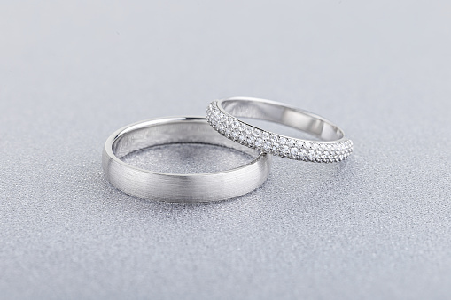 Pair of silver wedding rings on gray background. White gold ring bands with diamonds on female ring and matte textured surface on male ring. Advertising jewelry still life