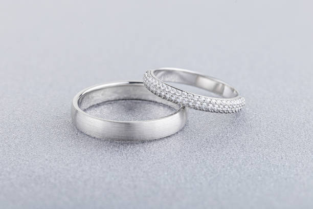 Pair of silver wedding rings on gray background