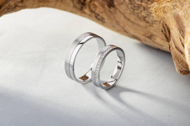 Pair of silver wedding rings with diamonds on gray background with wood