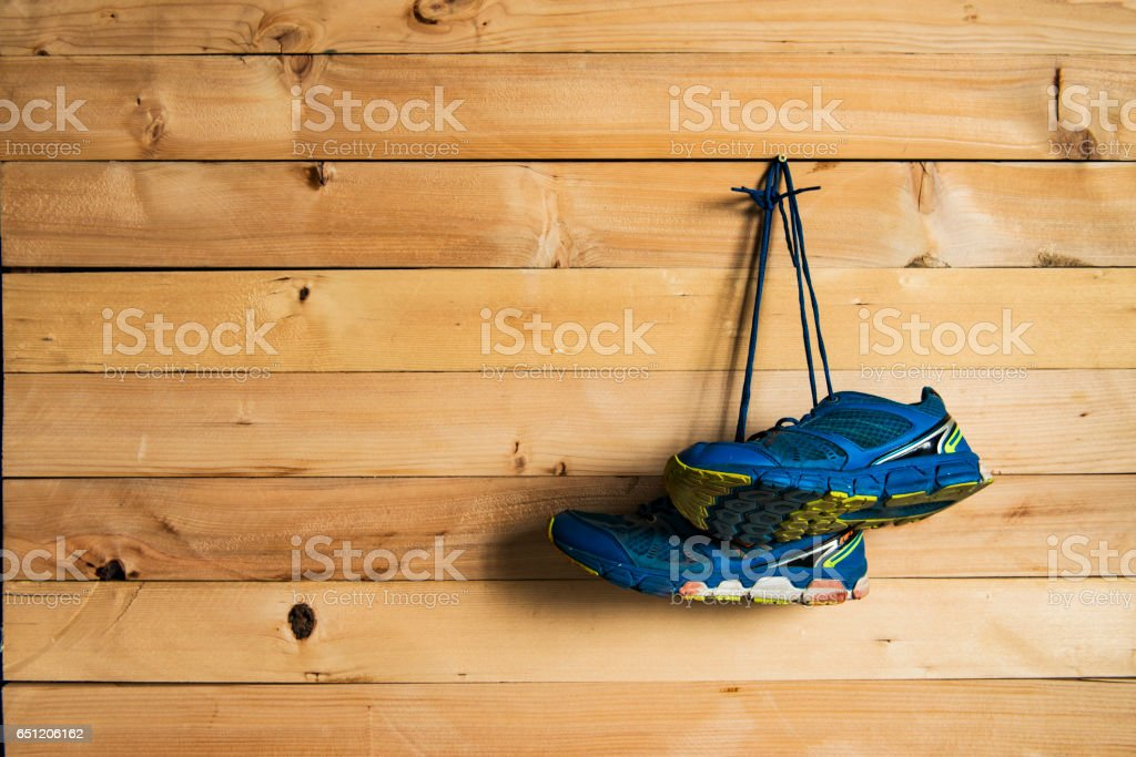 Pair of sneakers hang on a nail on a wooden fence background stock photo