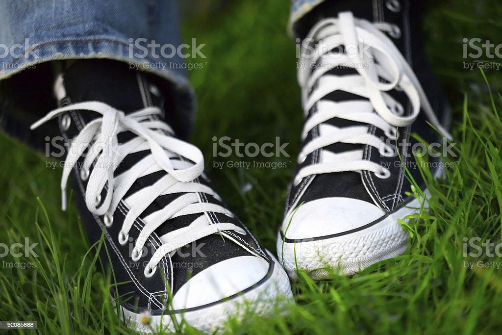 pair of sneakers in green grass royalty-free stock photo