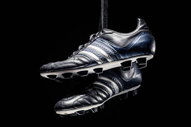 Pair of soccer shoes hanging on black background Pair of soccer shoes hanging on black background studded stock pictures, royalty-free photos & images