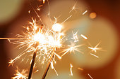 A pair of sparklers burn with a soft yellow light, scattering small stars of sparks around them