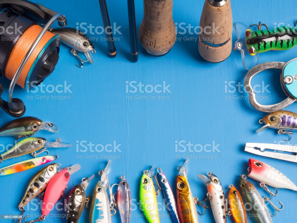 A pair of spinnings, a reel and baits and tools on a blue wooden background.Top of view royalty-free stock photo