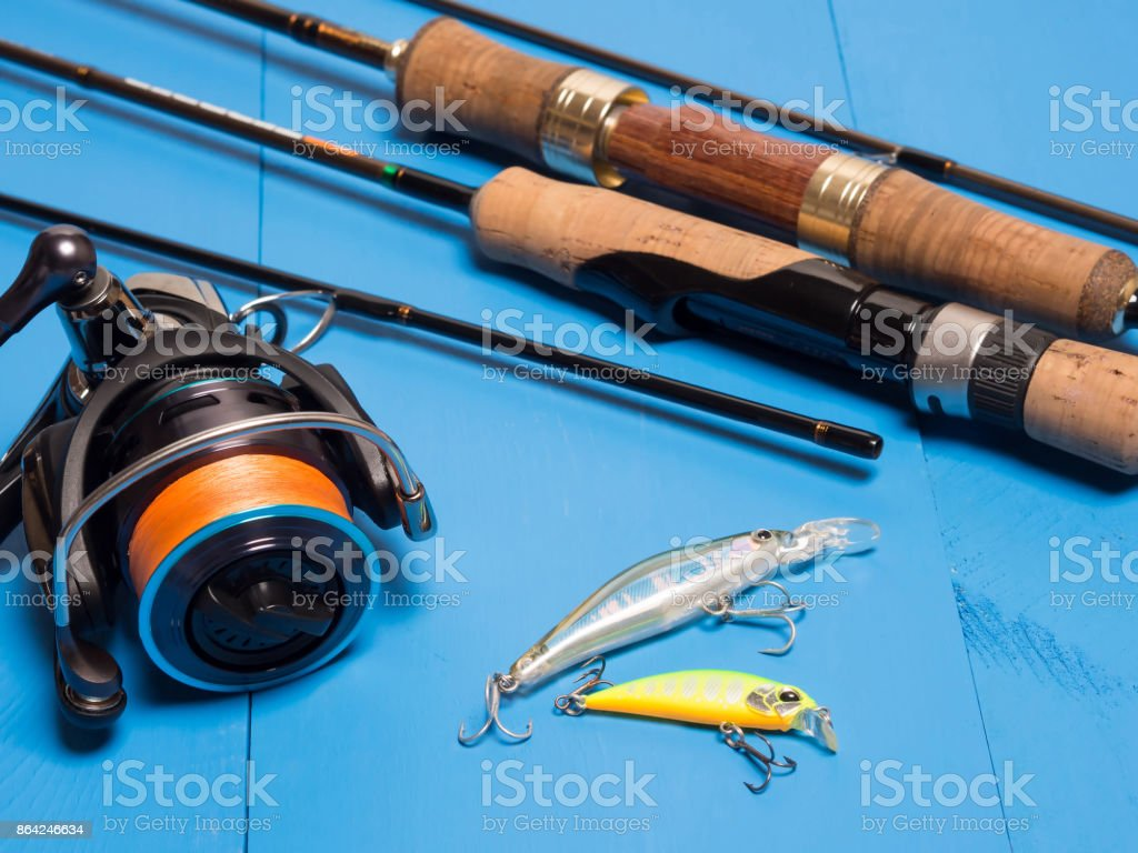 A pair of spinnings, a reel and baits on a blue wooden background.Top of view royalty-free stock photo
