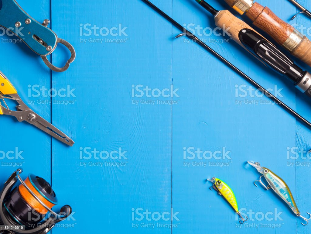 A pair of spinnings, a reel and lures on a blue wooden background.Top of view. Copy space. royalty-free stock photo