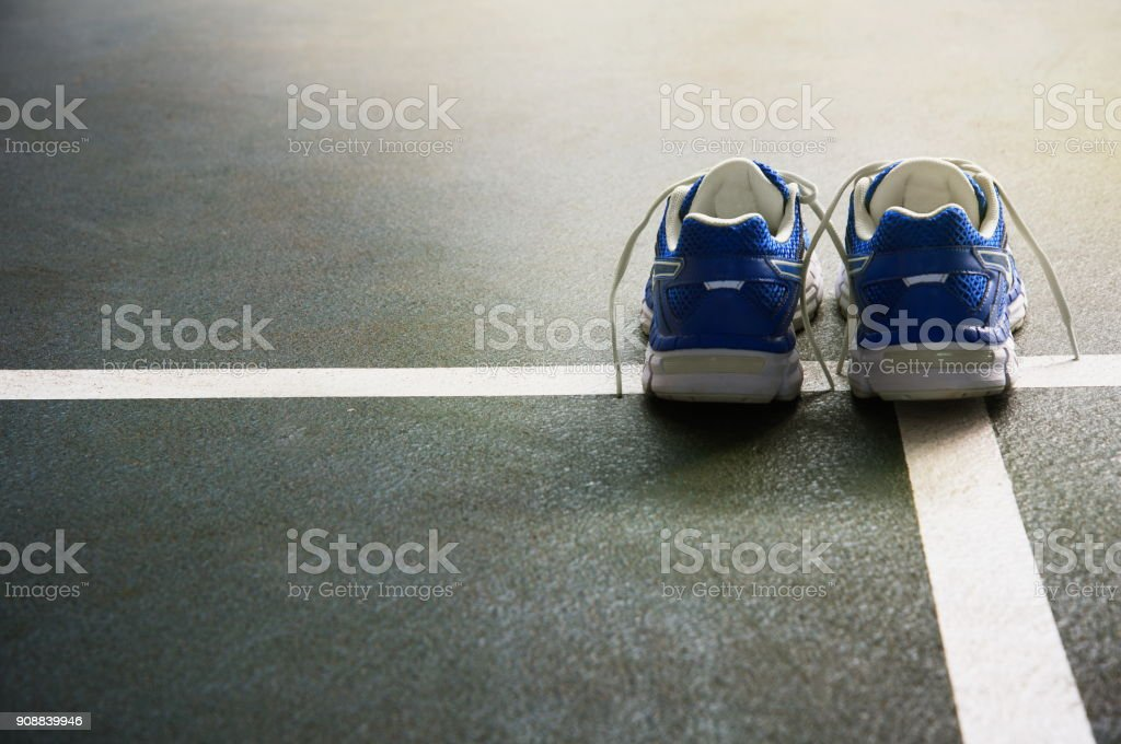 pair of sport shoes for running or active exercise for health on the dark green floor gymnasium with white line background stock photo