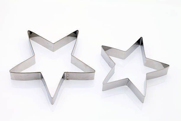 A pair of star shaped metal cutters isolated on white Star shaped cookie cutter on white background cookie cutter stock pictures, royalty-free photos & images