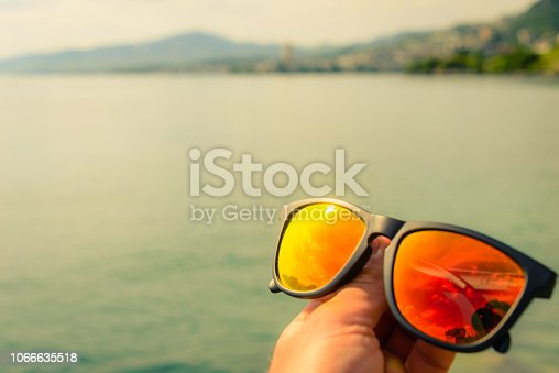 Holding a pair of sunglasses beside a lake in Switzerland with sun bouncing off the orange lenses