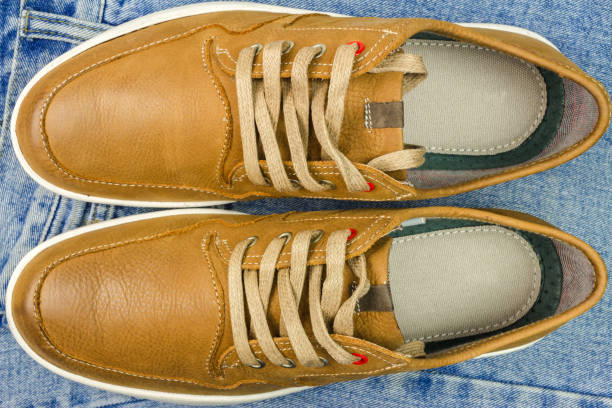 Pair of tan color, leather sneakers on jeans background, top view. stock photo