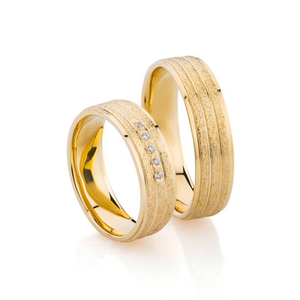 Pair of textured surface gold wedding ring bands isolated on white background