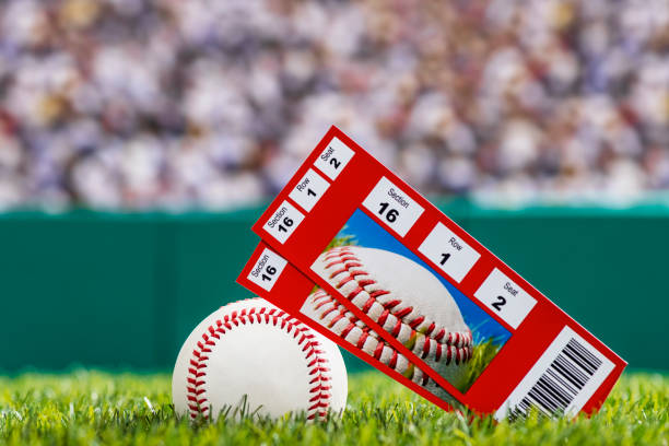 A pair of ticket stubs sitting on a baseball in the grass of a stadium stock photo