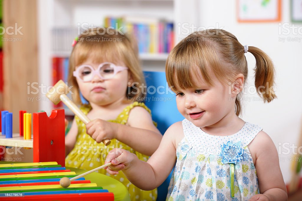Pair Of Toddlers Enjoying Music/ Playtime In A Nursery Setting stock photo