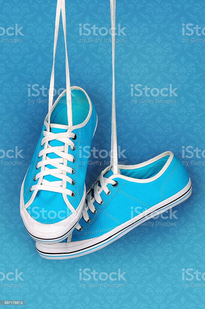 Pair of turquoise sneakers hangs on the laces. stock photo