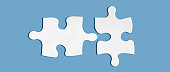 istock Pair of two matching puzzle pieces isolated on blue background. Successful decision, solution of problem. 1266381485