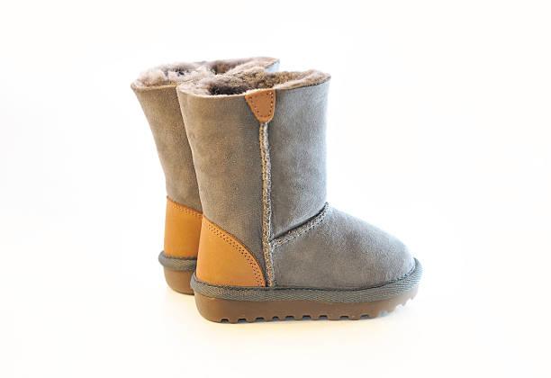 paar warmer winterstiefel in grauen pelz. - lammfellstiefel stock-fotos und bilder