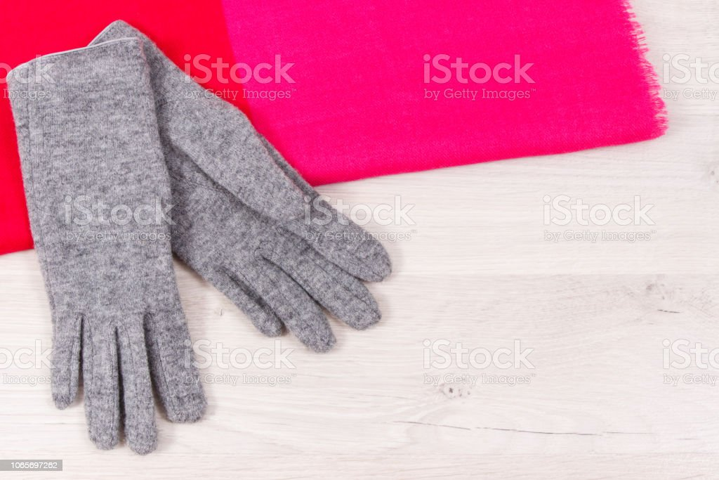 Pair of warm womanly gloves and shawl for using in autumn or winter