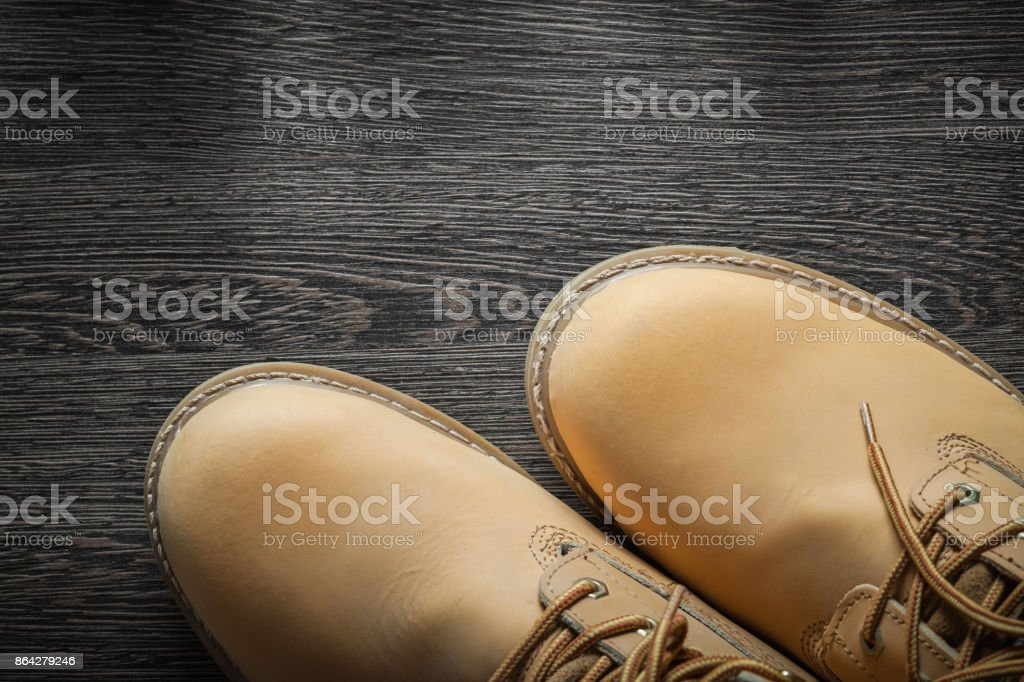 Pair of waterproof working boots on vintage wooden board royalty-free stock photo