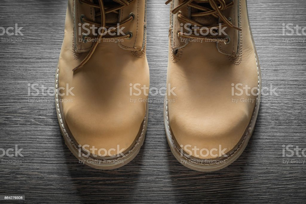 Pair of waterproof working boots on wooden board royalty-free stock photo