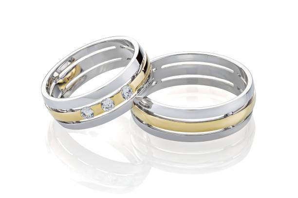 Pair of wedding silver ring and gold rings decorated with diamonds isolated on white background stock photo
