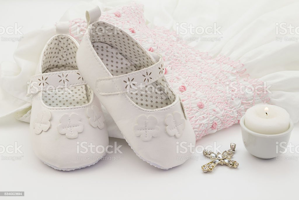 Pair of white baby shoes on embroidered christening white dress, stock photo