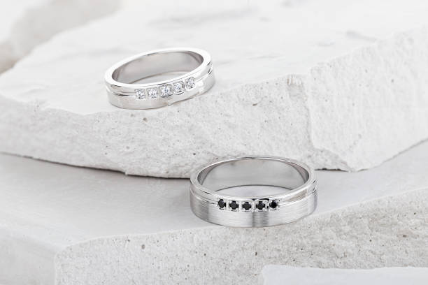 Pair of white gold wedding rings with diamonds on white textured background