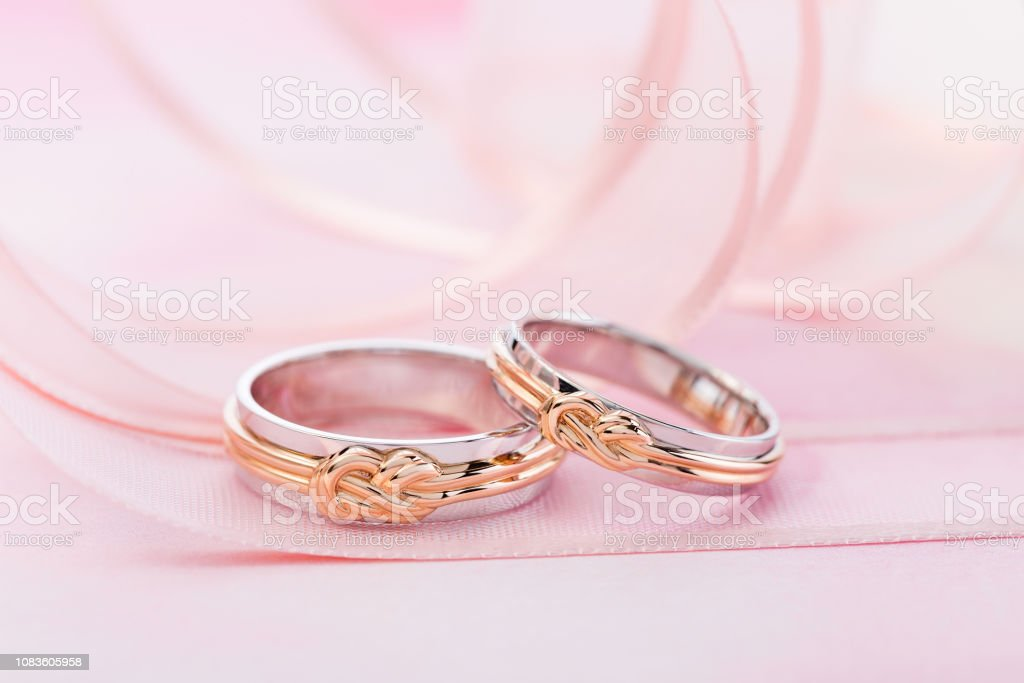 Pair of white gold wedding rings with pink gold knot on pink...