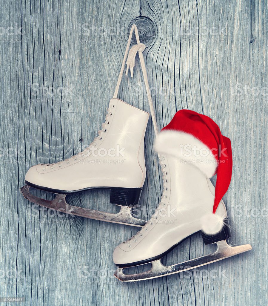 Pair of White Ice Skates and Santa Claus hat stock photo