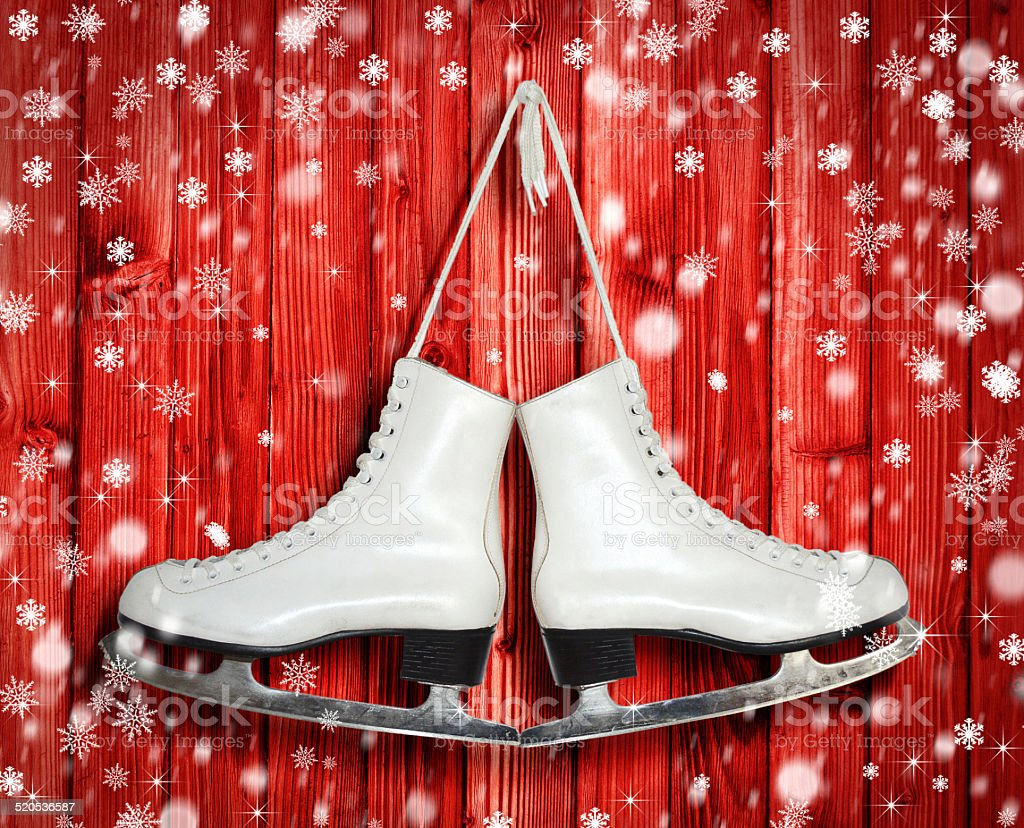 Pair of White Ice Skates on red wooden backround stock photo