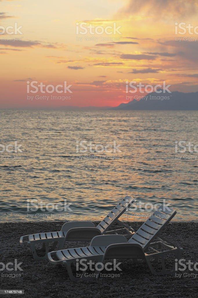 pair of  white plastic sunbed against mediterranean ocean sunset royalty-free stock photo