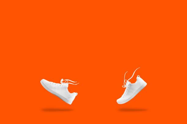 par vita sneaker sammansättning gillar promenader och flytande rep isolerad på orang bakgrund med urklippsbana - street dance bildbanksfoton och bilder