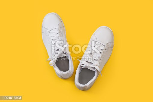 A pair of white sneakers on a yellow background in a top view