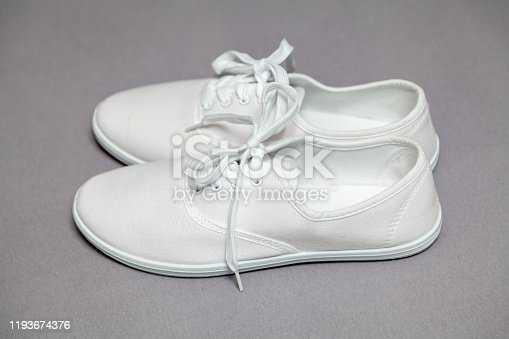Two new white sneakers with laces stand on a gray isolated background. Laces tied in a common knot