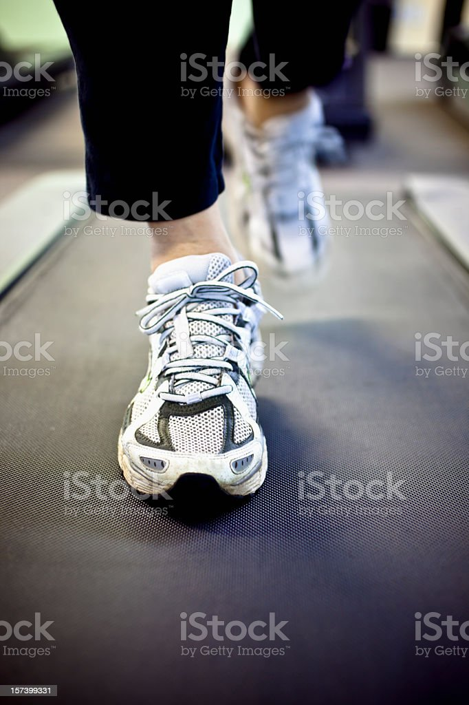 A pair of white trainers on a treadmill royalty-free stock photo