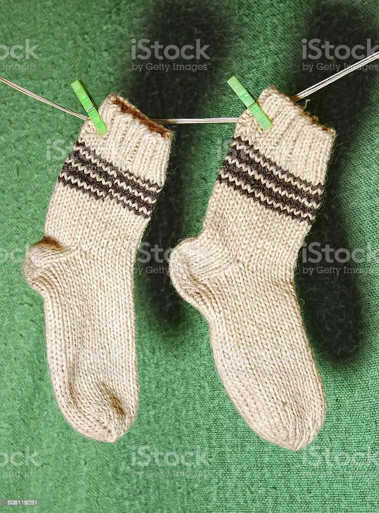 pair of white wool socks on a clothesline stock photo