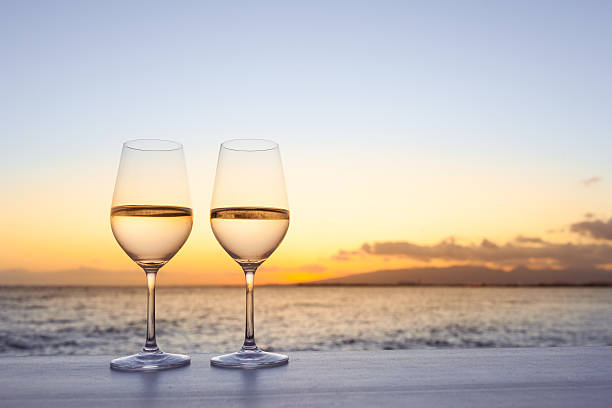 Pair of wine glasses on the beach. stock photo