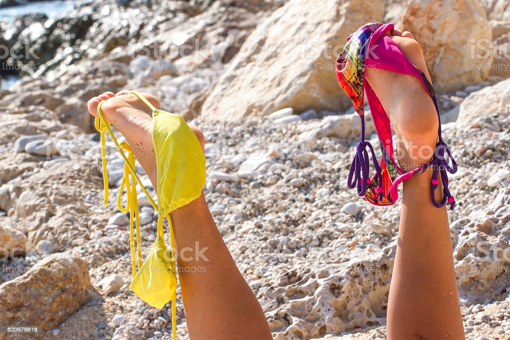 Pair of women's legs raised up. Swimsuit stretched on foto royalty-free