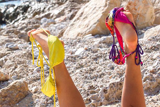 pair of women's legs raised up. swimsuit stretched on - fkk strand stock-fotos und bilder