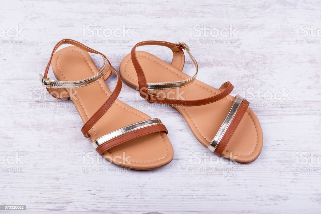 Pair of women's sandals on a white wooden background. stock photo