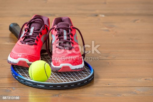 istock Pair of women's sneakers on a tennis racket on a wooden floor 687313166