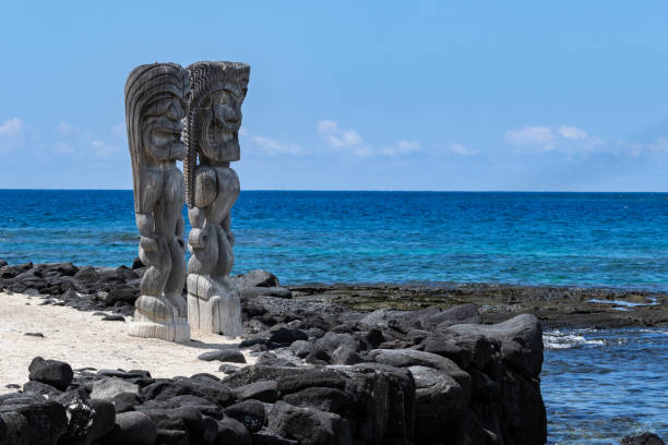 Pair of wooden status (Tikis), place of refuge (Honaunau), Hawaii. Standing on white sand, next to barrier wall of black lava rock. Blue Pacific ocean & sky in background. Two Wooden Tikis in the place of refuge (Honaunau) sanctuary, on the Big Island of Hawaii. Standing in white sand with a black lava barrier wall; Pacific ocean and blue sky are in the background. big island hawaii islands stock pictures, royalty-free photos & images