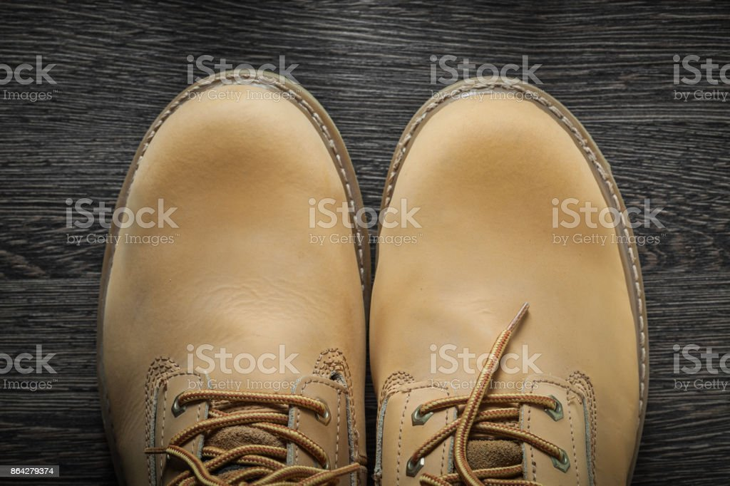 Pair of working boots on vintage wooden board royalty-free stock photo