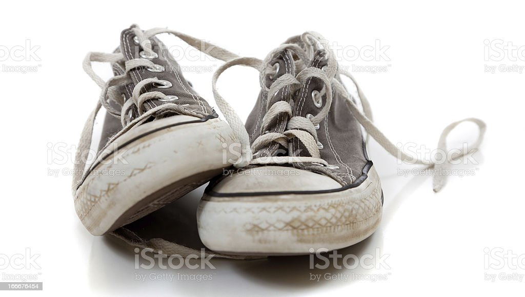 Pair of worn out gray sneakers on a white background royalty-free stock photo